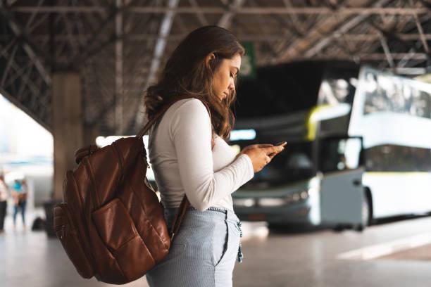 frau wartet am busbahnhof auf bus - tour bus stock-fotos und bilder