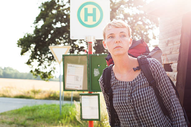 Frau wartet auf Bus A woman waits for the bus. frau stock pictures, royalty-free photos & images