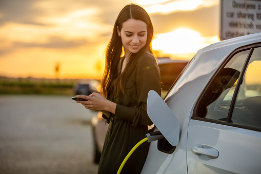 Side view waist up shot of a young woman in a dress using her mobile phone while waiting for her white electric car to charge during sunset
