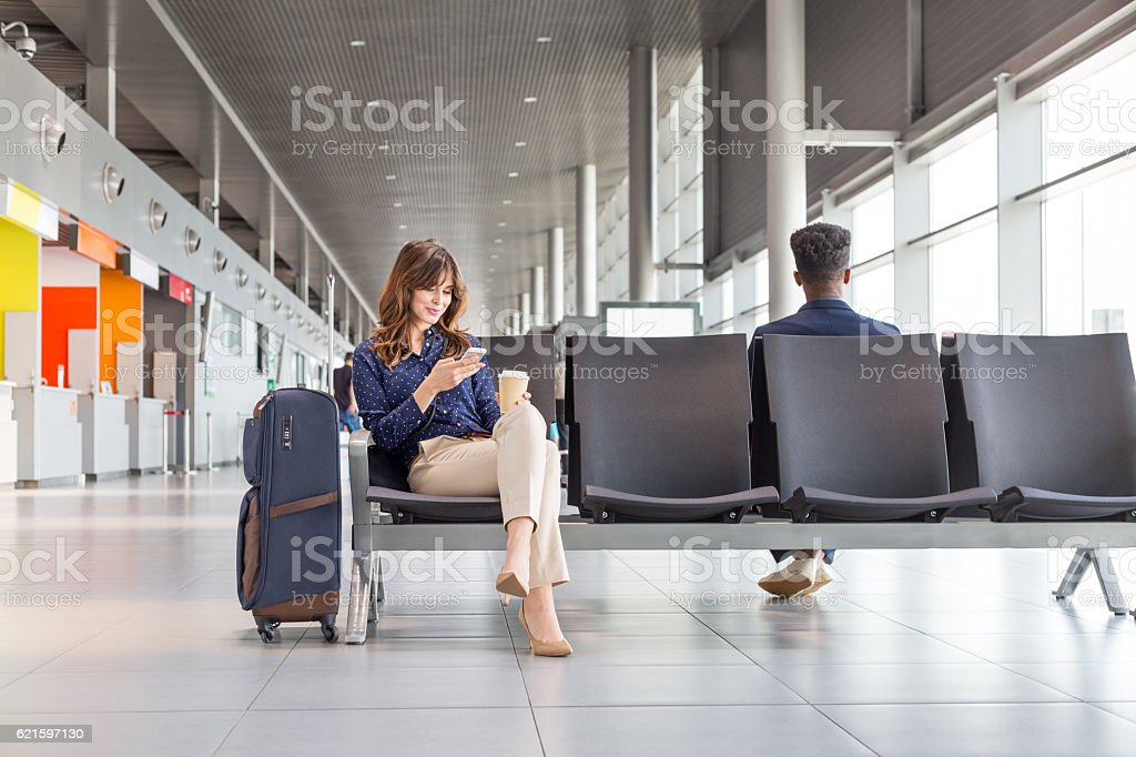 Woman waiting for flight at the airport lounge stock photo