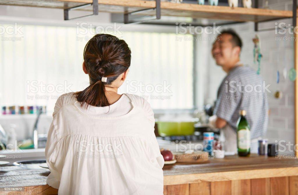 出てくる夫の料理を待っている女性。 ストックフォト