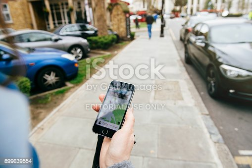 istock Woman waiting for the uber car on the street holding smartphone 899639554
