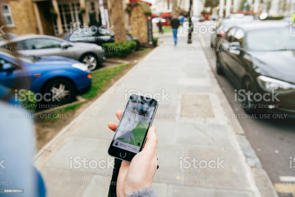 Woman waiting for the uber car on the street holding smartphone stock photo
