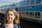 Headshot of Woman waiting for train outside at train station of Kutna Hora during day of springtime