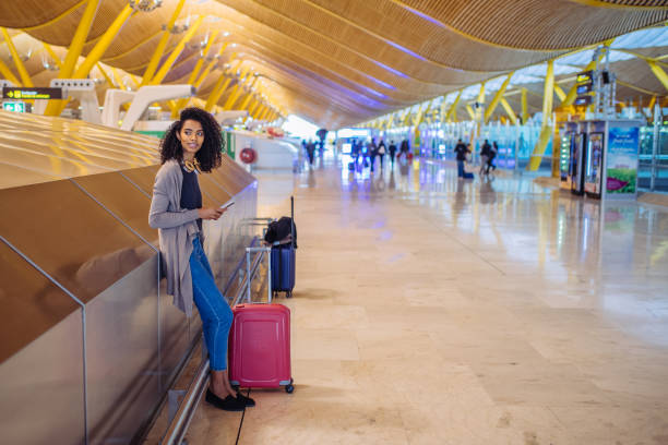 vrouw te wachten op haar vlucht met behulp van mobiele telefoon op de luchthaven - airport pickup stockfoto's en -beelden