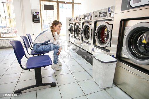 958801774 istock photo Woman waiting in a laundry room 1195411512