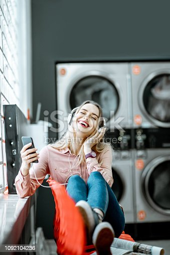 958801774 istock photo Woman waiting in the self-service laundry 1092104236
