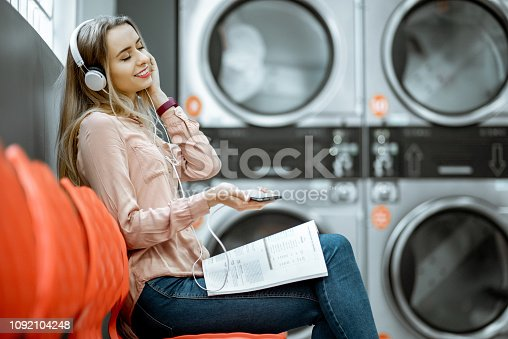 958801774 istock photo Woman waiting in the self-service laundry 1092104248