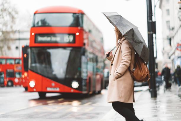 Frau wartet auf einem Busbahnhof, während Doppeldeckerbus nähert – Foto