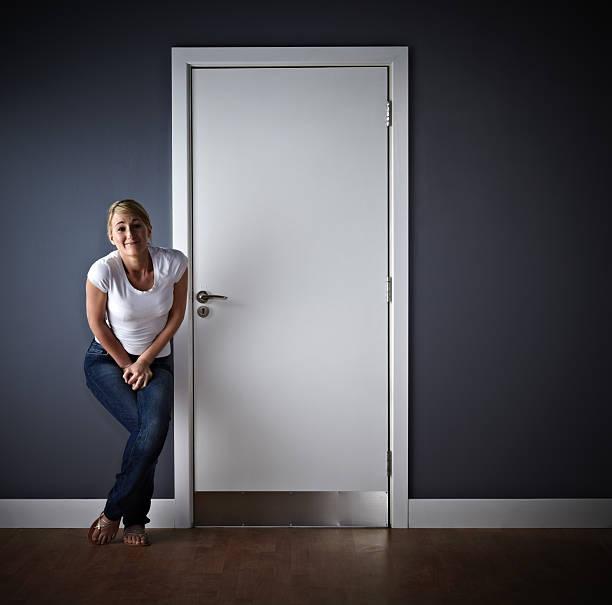 Woman waiting outside ladies toilet stock photo