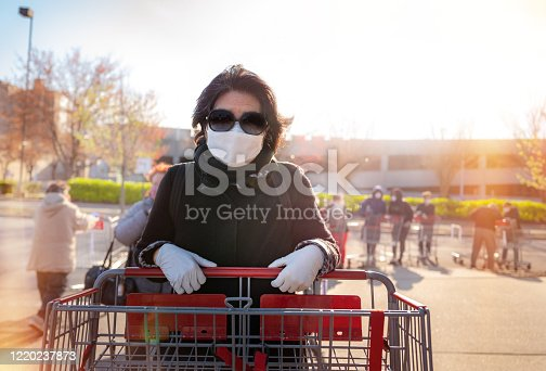 Senior woman waiting for supermarket store to let her in to shop for supplies.  The store allows seniors first, but they must wait outside until the store clears of customers.