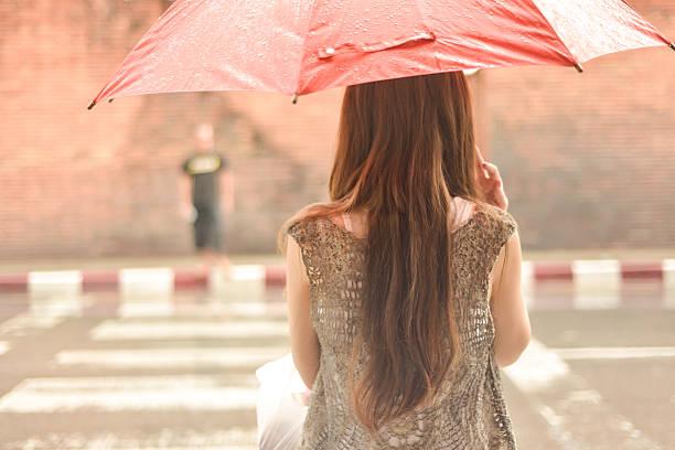 frau warten auf sie im regen mit regenschirm street - regenzeit stock-fotos und bilder