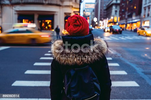 Woman waiting to cross the street in downtown Manhattan - New York City, USA.