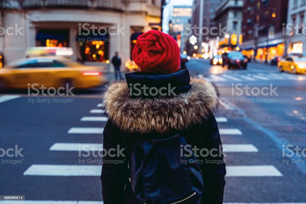 Woman waiting to cross the street in downtown Manhattan - New York City stock photo