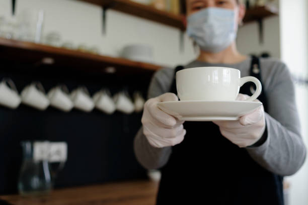 Woman waitress with cup in face mask and gloves