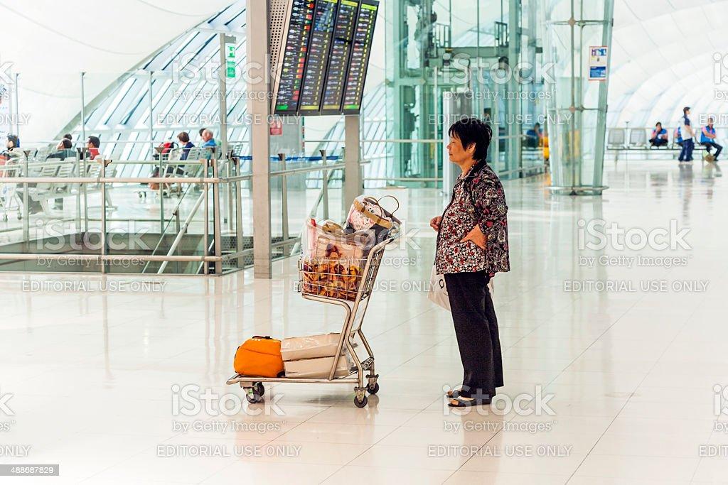 woman waits with baggage cart  at Suvarnabhumi International Air stock photo