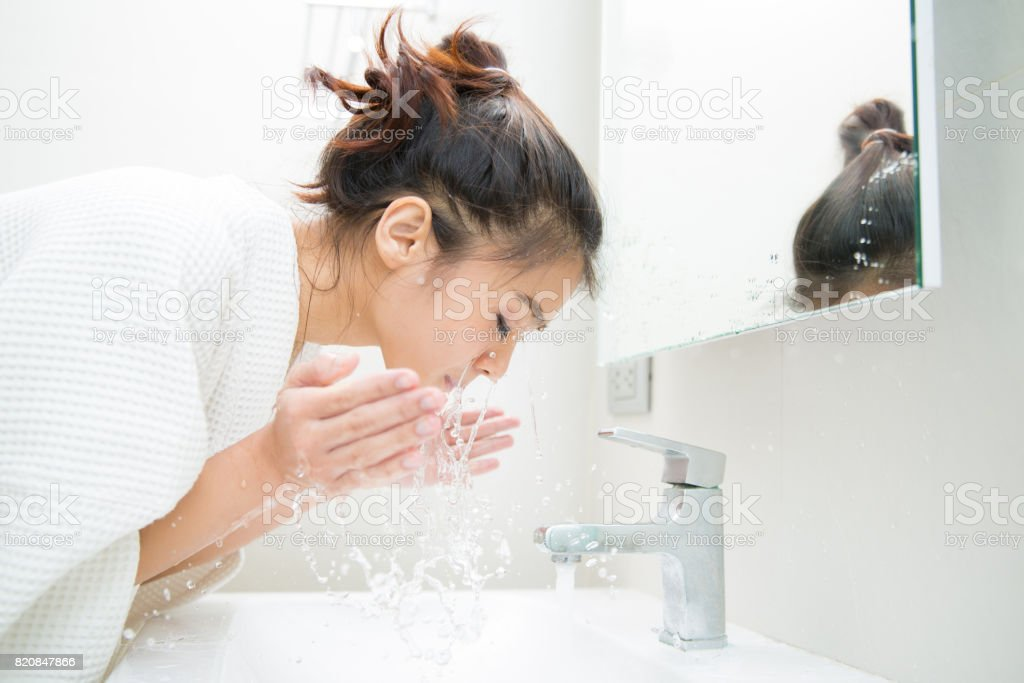 Woman wakes from sleep and she was cleansing the morning before shower stock photo