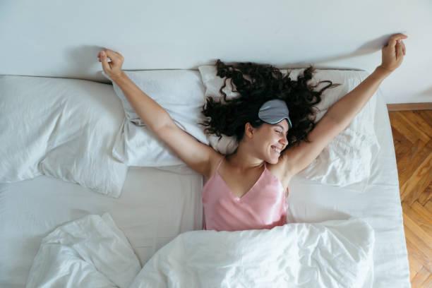 woman waking at the bright morning. sleeping mask stock photo