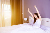 Woman waking up and hand raised on bed in bedroom