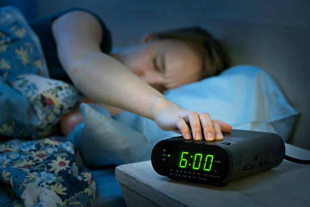 woman waking up early with alarm clock - een dutje doen stockfoto's en -beelden