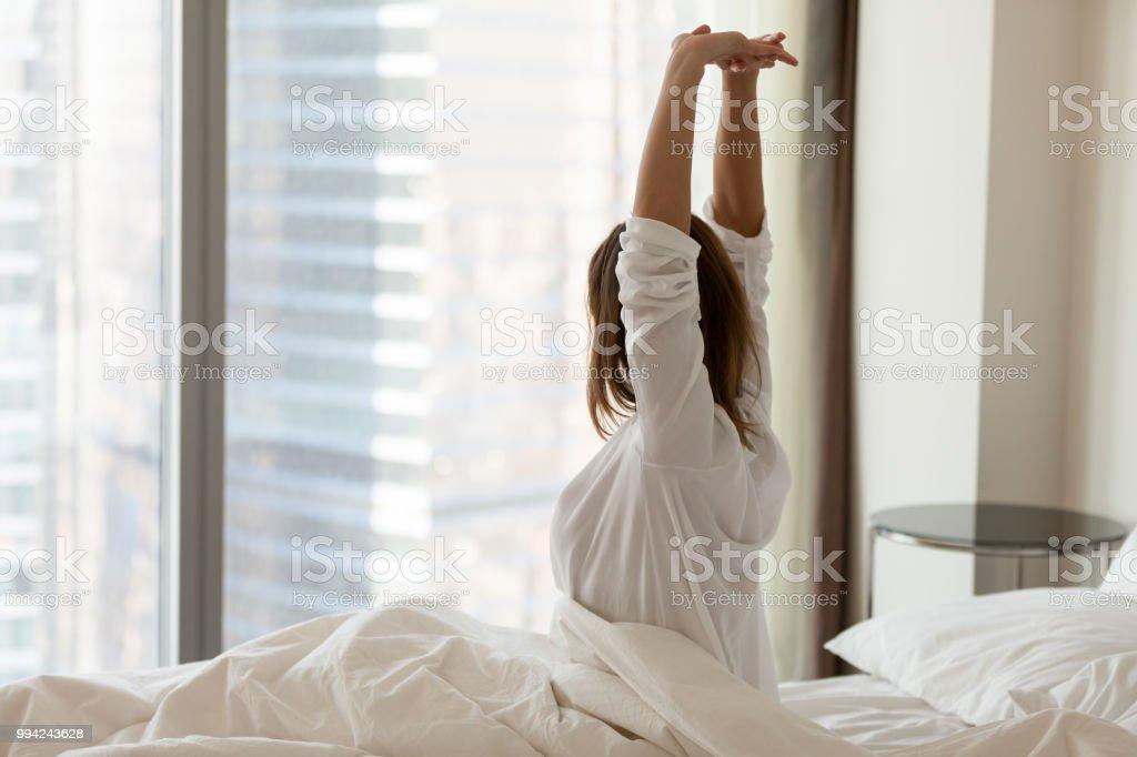Femme réveiller heureux qui s'étend sur un lit confortable dans l'hôtel - Photo