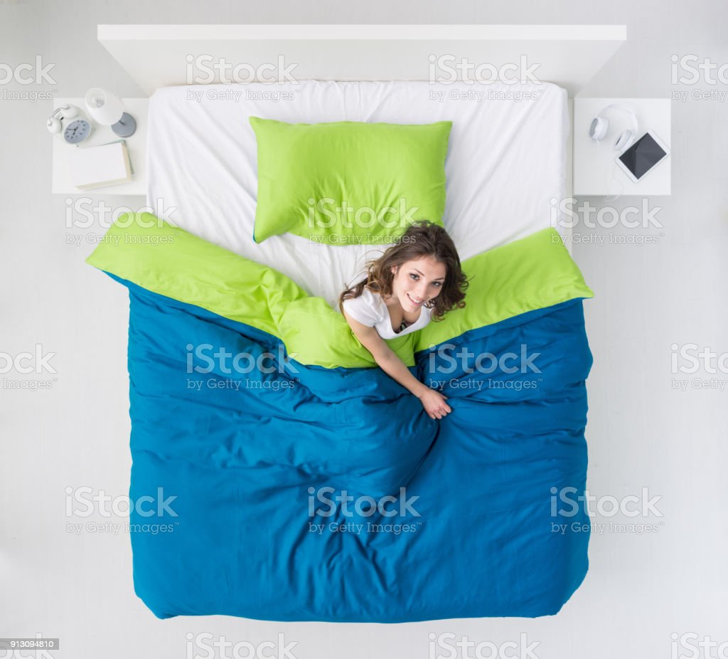 Woman waking up in her bed stock photo