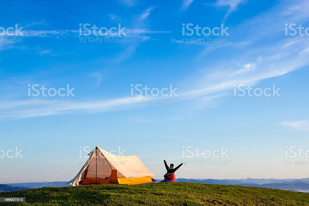 Woman Waking Up on a Mountain Woman Waking up with the arms up in the air after a night on the top of a Mountain 2015 Stock Photo