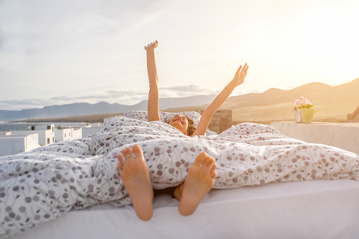 istock Woman waking up outdoors on the rooftop 515833680