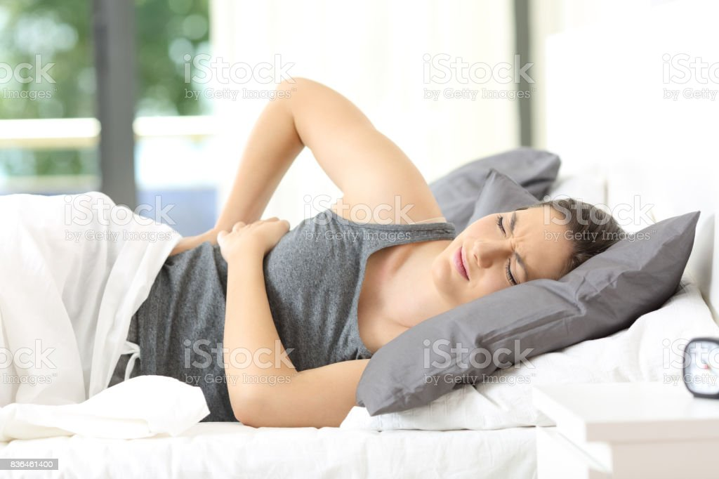 Woman waking up suffering back ache stock photo