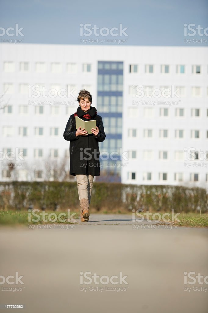 woman walk and reading stock photo