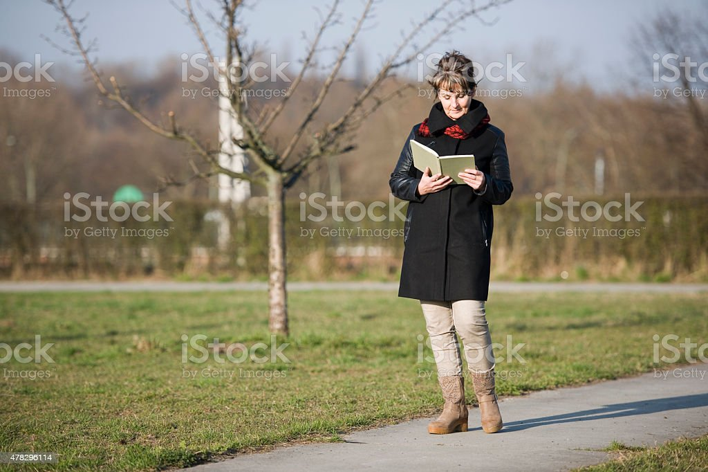 woman walk and reading side stock photo