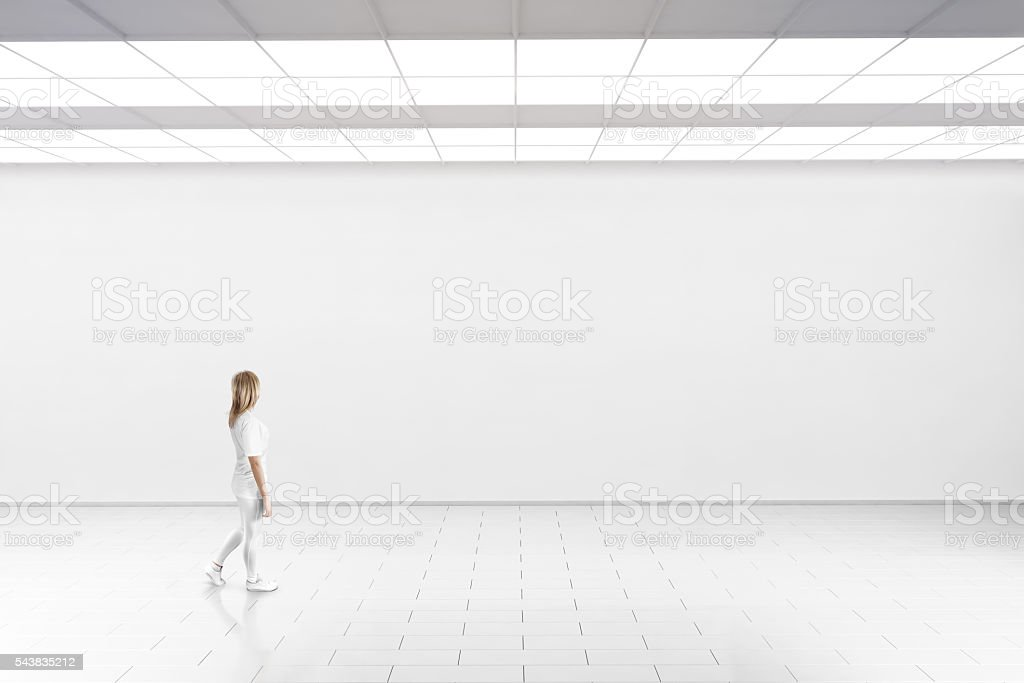 Woman walk in museum gallery with blank wall.圖像檔