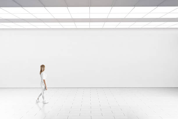Woman walk in museum gallery with blank wall. stock photo