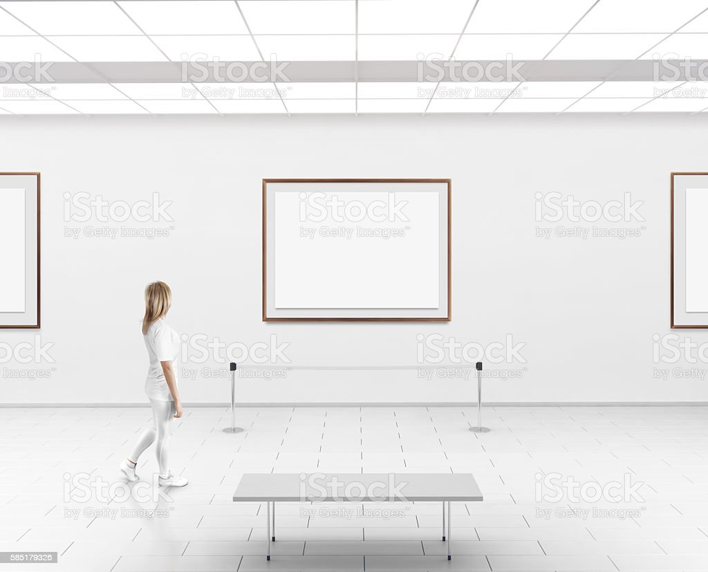 Woman walk in museum hall blank wall with frames stock photo