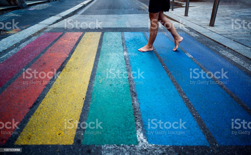Woman walk over a pedestrian crossing in rainbow colors stock photo