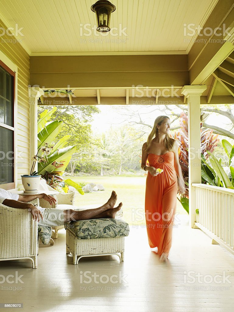 Woman walking across porch of tropical home royalty-free stock photo