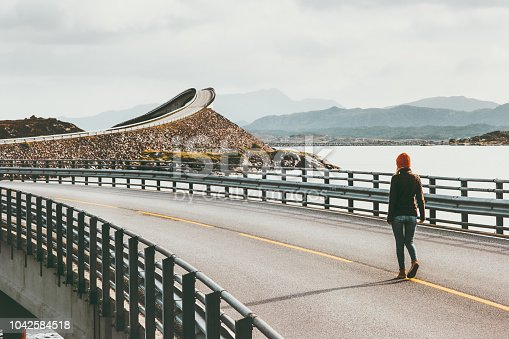 istock Woman walking alone at Atlantic road in Norway Storseisundet bridge Travel Lifestyle concept adventure vacations outdoor 1042584518