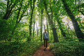 istock Woman walking alone in the forest 1246205611