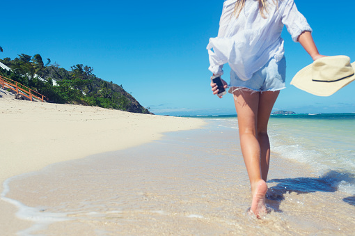 Woman walking alone on a beach.