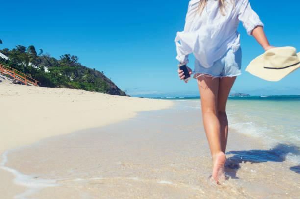 Woman walking alone on a beach. stock photo