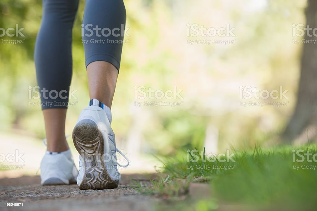 Woman walking along a pathway in the park stock photo