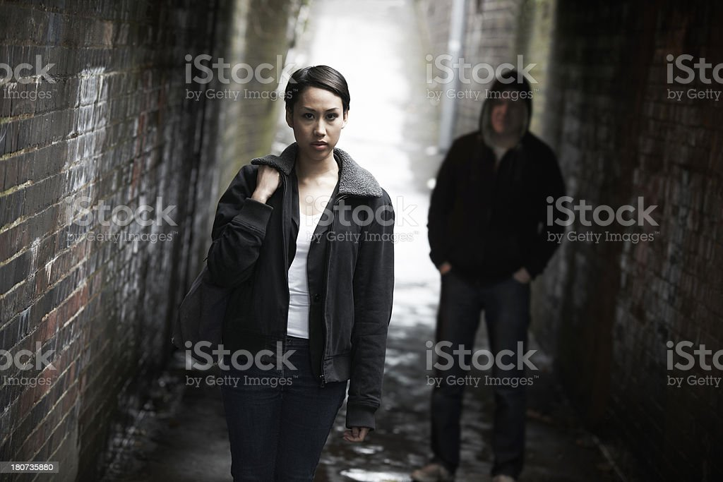Woman Walking Along City Street With Figure In Shadows Behind stock photo