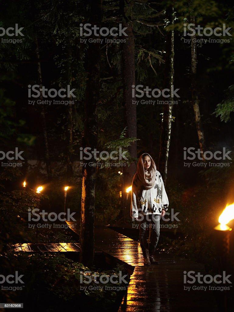 Kobieta spaceru wzdłuż ścieżki w deszczową noc. zbiór zdjęć royalty-free