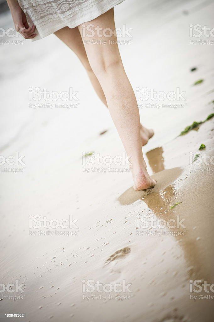 Woman walking along the beach stock photo