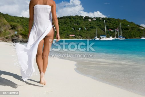 rear shot of young woman in white bikini and sarong walking along the shore in Jost van Dyke, British Virgin Islands