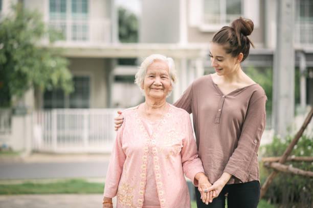 woman walking and embracing Asian elderly woman stock photo