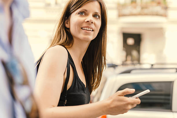 woman walking and holding mobile phone - kvinna cloes up bildbanksfoton och bilder