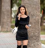 istock Woman walking and talking on phone 1186891634