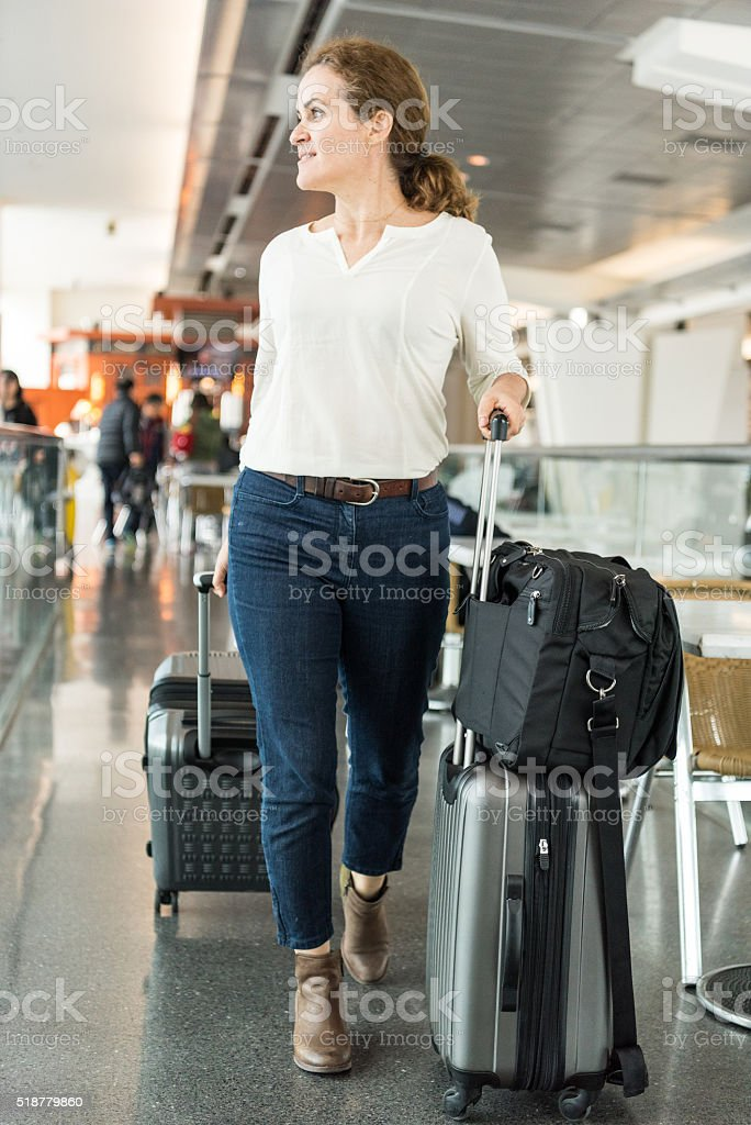 Woman walking at the airport walkway pulling rolled-on suitcases stock photo