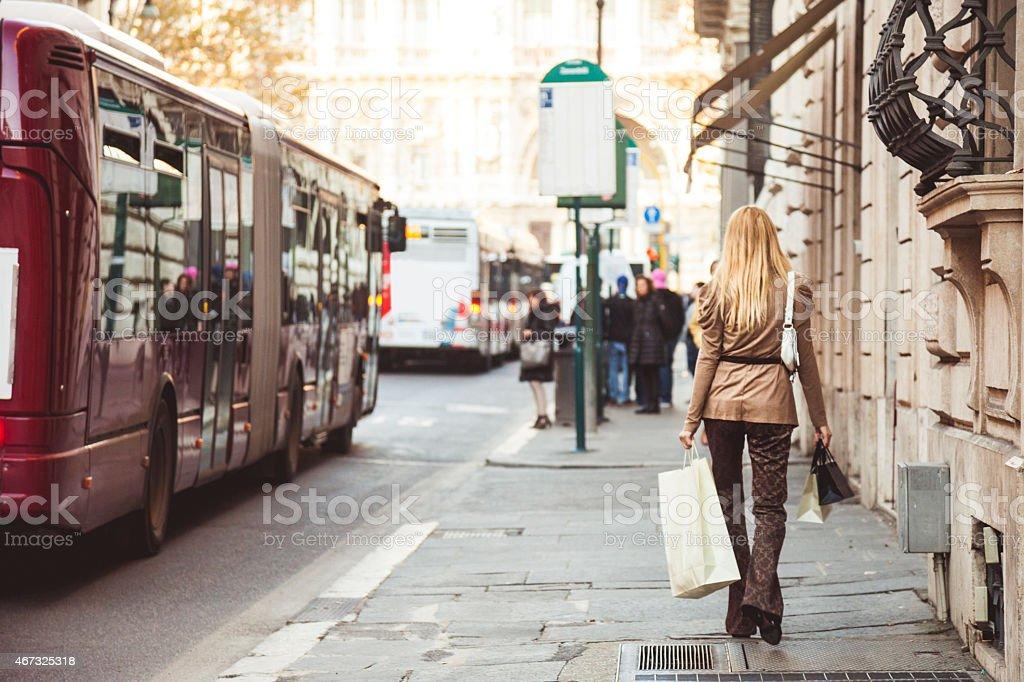 Donna camminare alla fermata dell'autobus con le borse degli acquisti - foto stock